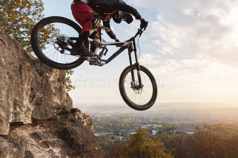 Um cavaleiro novo na roda de seu Mountain bike faz um truque no salto no trampolim da montanha em declive fotografia de stock royalty free