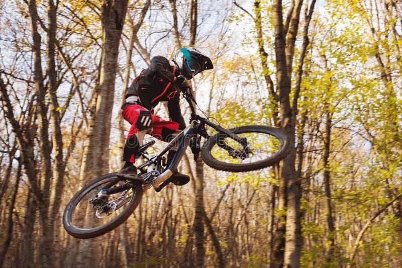 Um cavaleiro novo na roda de seu Mountain bike faz um truque no salto no trampolim da montanha em declive fotografia de stock