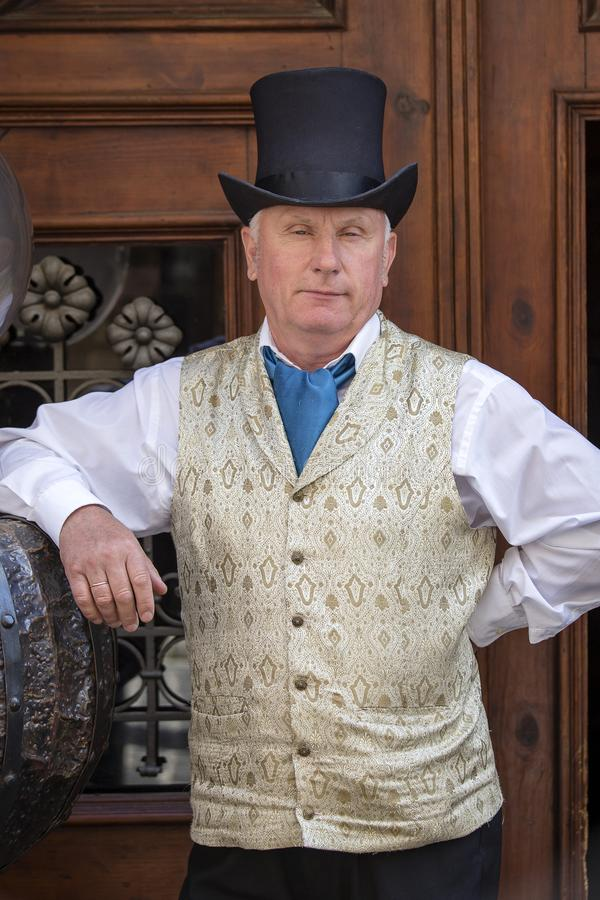 Um cavalheiro elegante do vintage retro à moda em um waistcoat e em um chapéu de jogador convida turistas a entrar no restaurante fotos de stock