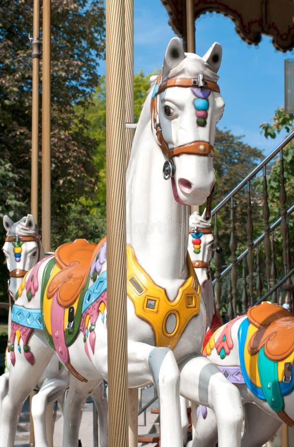 Um cavalo branco Prances no carrossel fotografia de stock