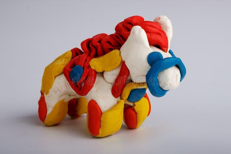 Um cavalo feito do plasticine em um fundo homogêneo imagem de stock