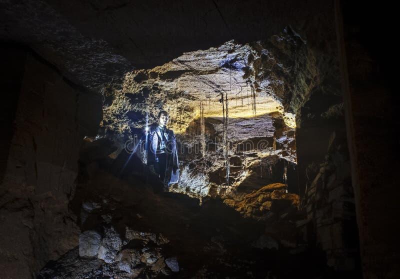 Um caver explora uma caverna com uma lanterna Odessa Catacombs, Ucrânia imagem de stock royalty free