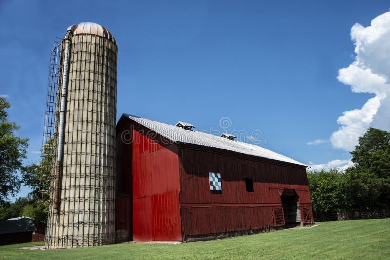 Um celeiro vermelho velho com um silo enorme senta-se na grama verde fotografia de stock royalty free