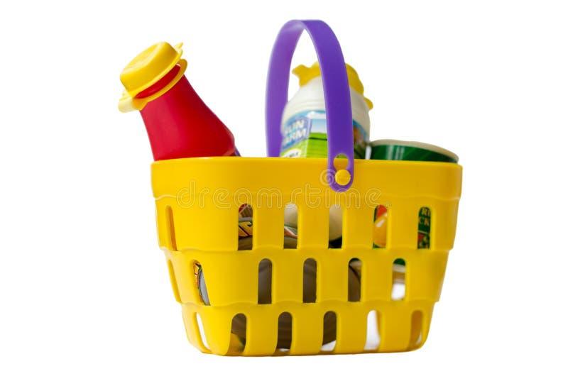 Um cesto de compras colorido do brinquedo enchido com os mantimentos Isolado no branco foto de stock