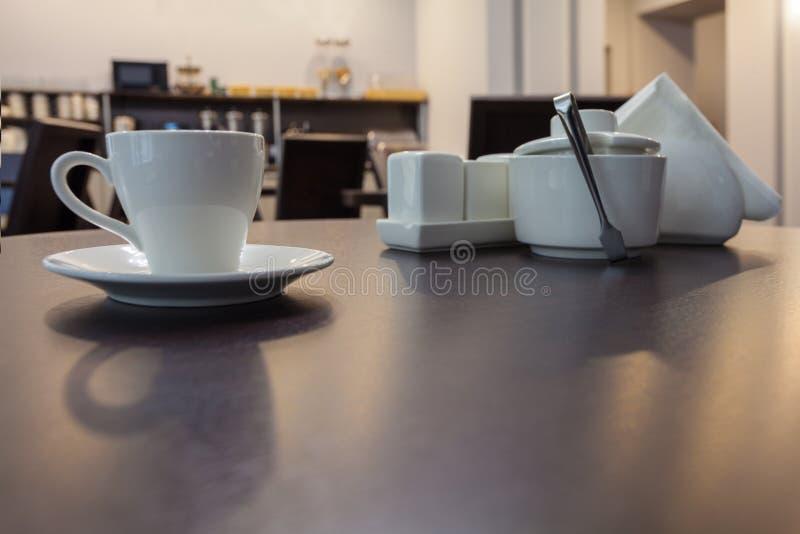 Um chá da xícara de café na mesa redonda de madeira no café moderno com mobília da cozinha no fundo fotos de stock royalty free