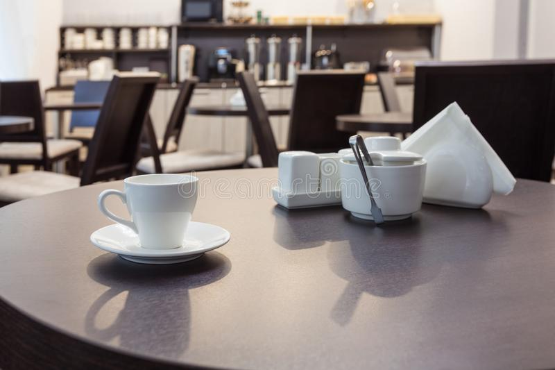 Um chá da xícara de café na mesa redonda de madeira no café moderno com mobília da cozinha no fundo interior imagem de stock