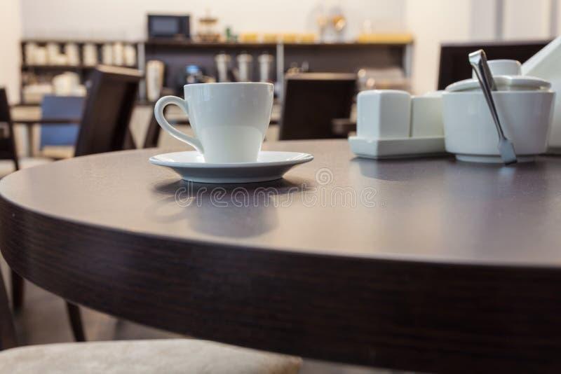 Um chá da xícara de café na mesa redonda de madeira no café moderno com mobília da cozinha no fundo interior imagens de stock