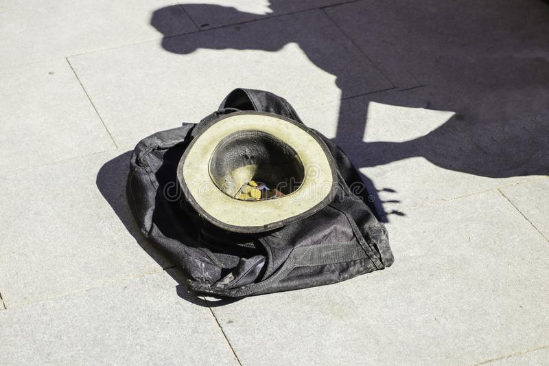 Um chapéu com moedas encontra-se no asfalto à sombra de um guitarrista da rua fotografia de stock royalty free