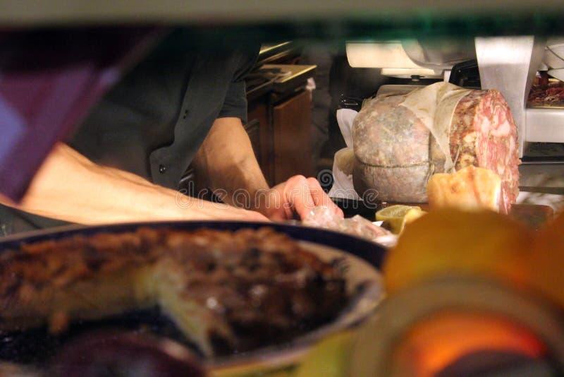 Um chefe em um restaurante local em Firenze prepara pratos italianos A vista é um de um assediador, ou um cliente potencial foto de stock royalty free