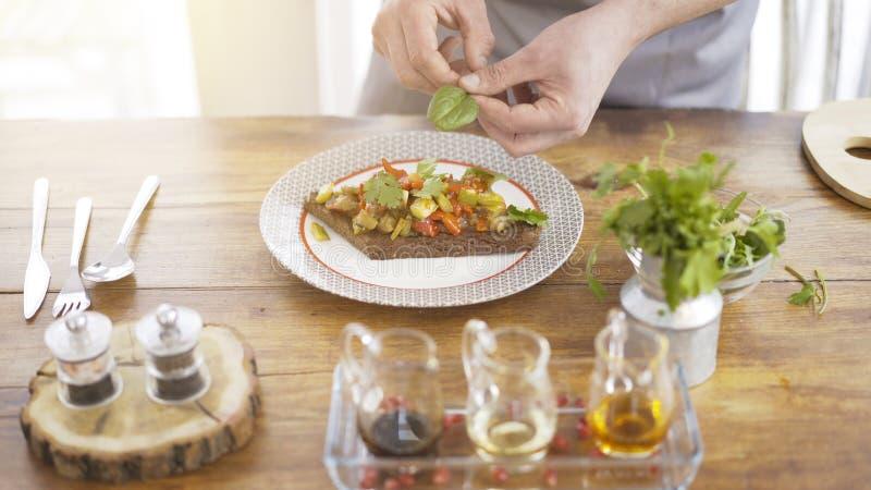 Um chefe masculino está adicionando as hortaliças a uma salada do guisado em uma parte de um pão preto fotografia de stock royalty free