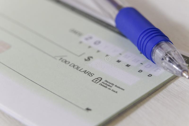 Um cheque pessoal vazio com uma pena imagem de stock