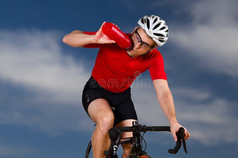 Um ciclista bebendo fotografia de stock royalty free
