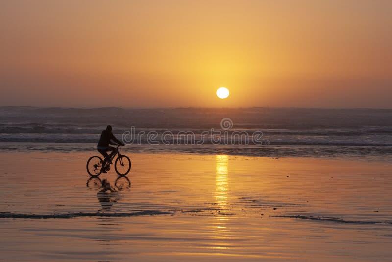 Um ciclista monta no por do sol na baía de Cox em Tofino, BC imagens de stock