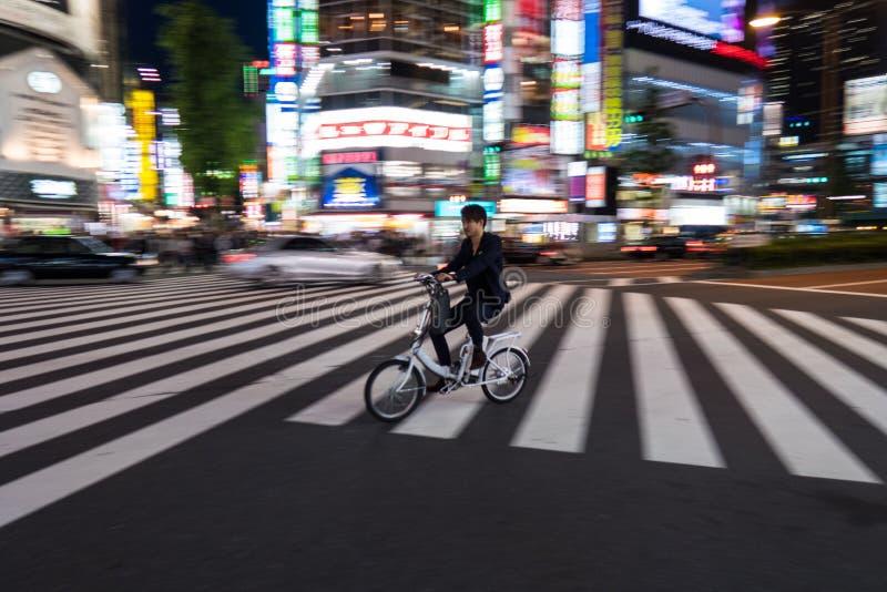 Um ciclista passa através do cruzamento de Shinjuku no Tóquio, Japão fotografia de stock royalty free
