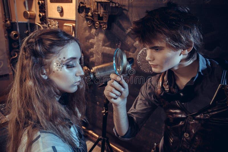 Um cientista novo olha uma menina em uma lupa imagens de stock