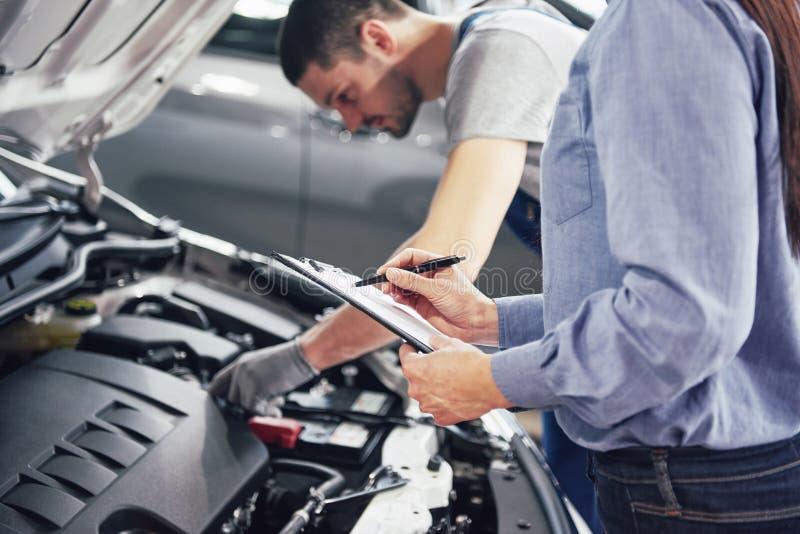 Um cliente do mecânico e da mulher do homem olha a capa do carro e discute reparos imagens de stock royalty free