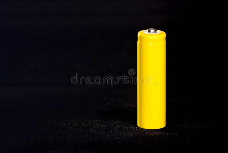 Um close-up amarelo da bateria em um preto escuro borrou o fundo electrics Bateria Acumulador na tela com villi fotos de stock