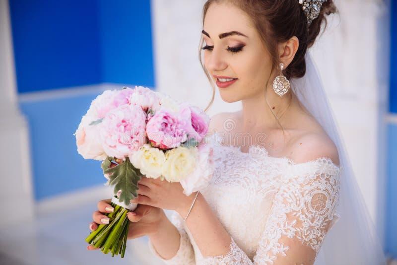 Um close-up da noiva respira no perfume de peônias cor-de-rosa e brancas A menina em um vestido de casamento com um ramalhete de foto de stock