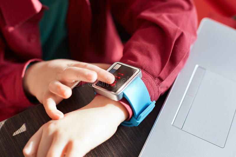 Um close-up das mãos do ` s da criança com relógio esperto Relógio eletrônico tocante Conceito Wearable do dispositivo Mostrando  imagem de stock