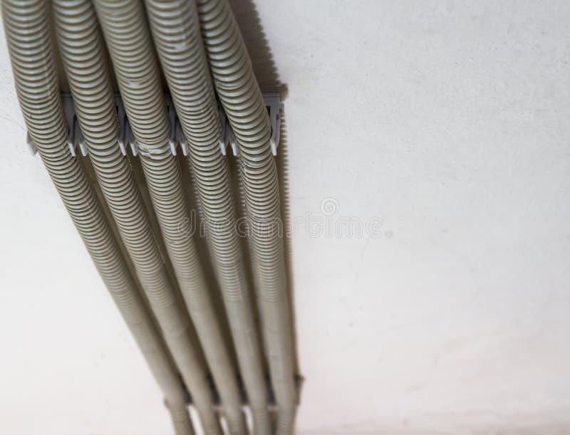 Um close-up de diversas tubulações cinzentas onduladas é fixado ao teto com grampos Tubulação ondulada do PVC do branco protetor fotos de stock