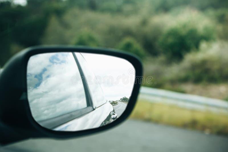 Um close-up de um espelho retrovisor do carro ao conduzir em uma estrada asfaltada ou em uma autoestrada imagem de stock royalty free