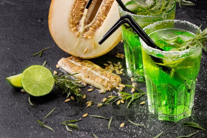 Um close-up de frutos exóticos Cocktail verdes do álcool com palhas Corte o melão Bebidas do estragão e cal fresco em um fundo pr imagens de stock
