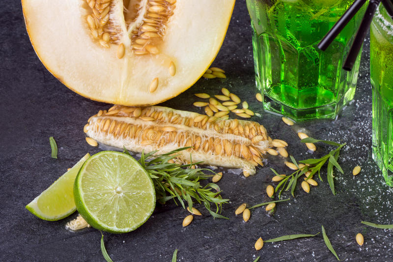 Um close-up de frutos exóticos Corte o melão Cocktail verdes do álcool com palhas Folhas do estragão e cal fresco em um fundo pre imagem de stock royalty free