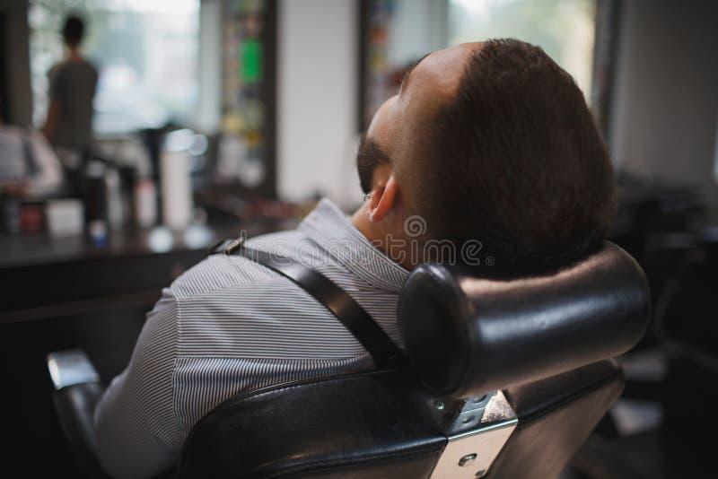 Um close-up de um homem considerável que senta-se em uma cadeira do ` s do cabeleireiro Um homem à moda novo com uma barba em um  imagem de stock