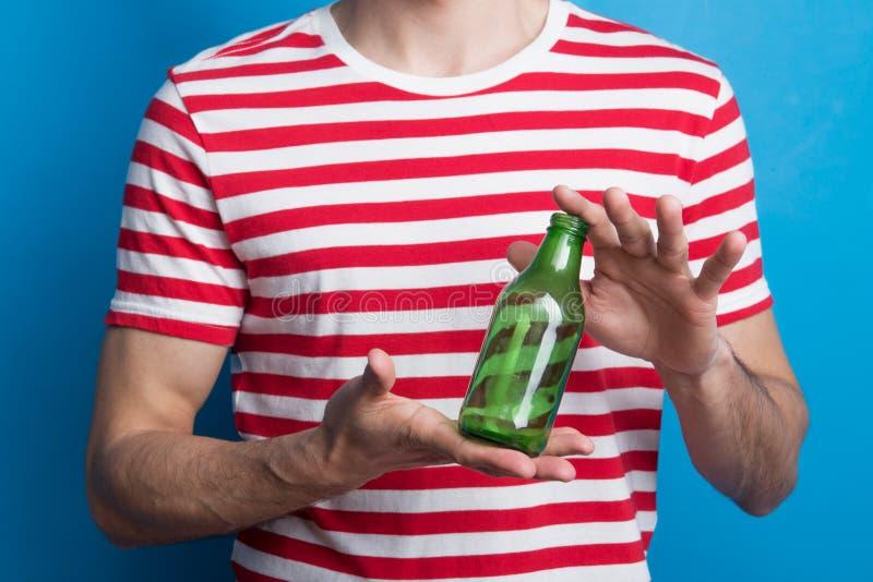 Um close-up de um homem irreconhecível em um estúdio que guarda uma garrafa vazia foto de stock royalty free