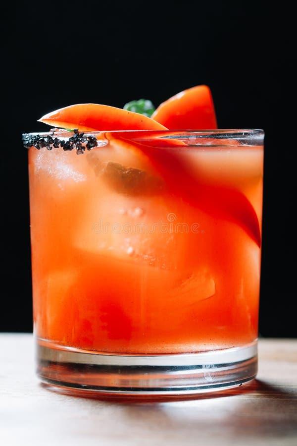 Um cocktail alcoólico decorado com pimentas de sino vermelhas, b do tequila imagem de stock royalty free