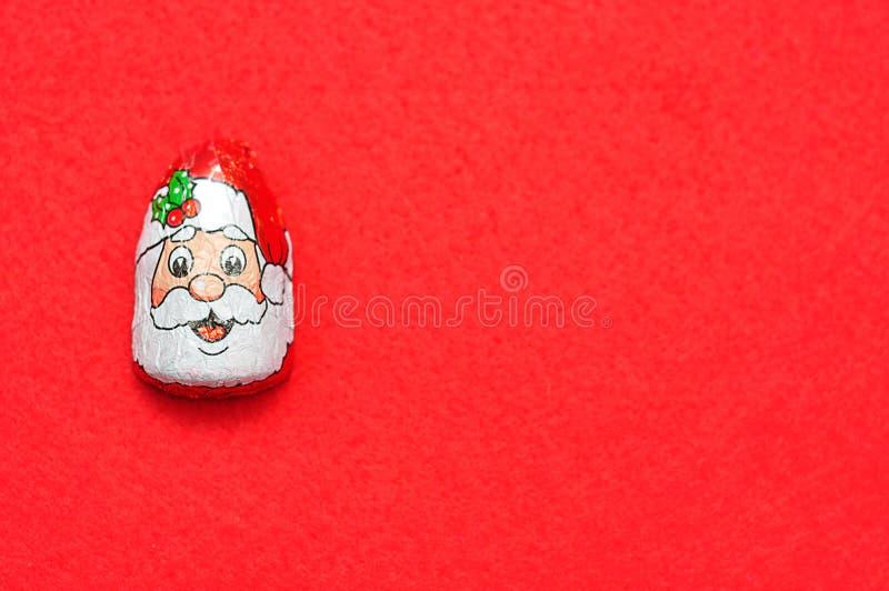 Um com cobertura em chocolate com o envoltório da cara do ` s de Papai Noel foto de stock