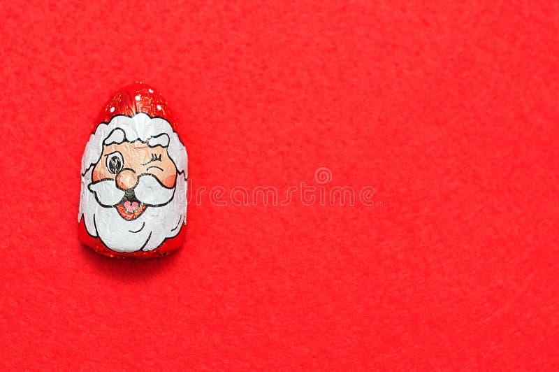 Um com cobertura em chocolate com o envoltório da cara do ` s de Papai Noel foto de stock royalty free