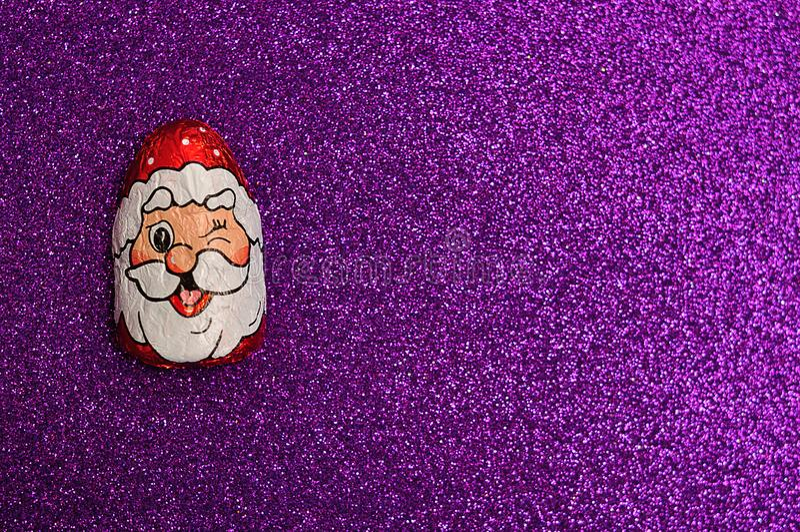 Um com cobertura em chocolate com o envoltório da cara do ` s de Papai Noel imagem de stock royalty free