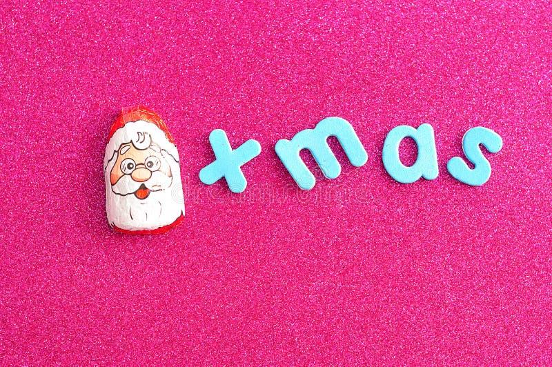 Um com cobertura em chocolate com Santa Claus enfrenta o envoltório com o xmas da palavra fotos de stock royalty free