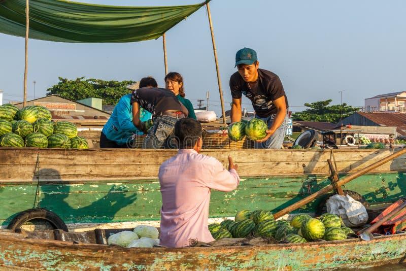 Um comerciante vende melancias a um revendedor na flutuação de Cai Rang foto de stock