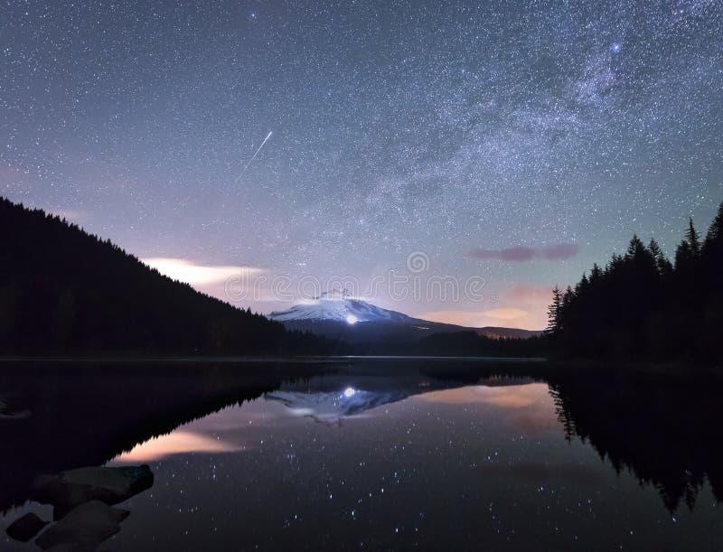 Um cometa e elevações da Via Látea acima da capa do Mt imagens de stock
