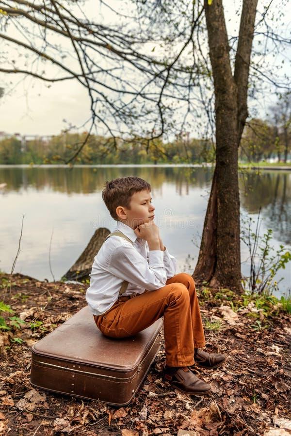 Um companheiro rústico de ninhada do simpleton que senta-se em uma mala de viagem antiquado retro no banco de um lago do rio imagens de stock
