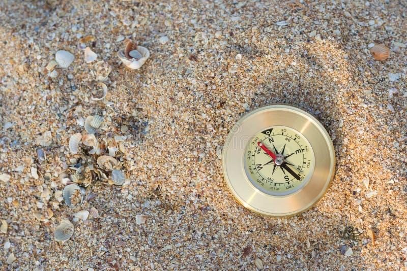 Um compasso que mostra o sentido encontra-se na areia do mar com shell imagem de stock