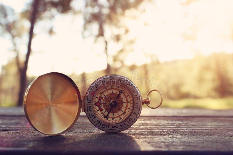 Um compasso sobre a tabela de madeira na luz do por do sol imagens de stock royalty free