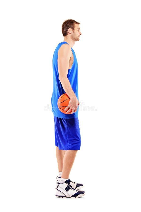 Um comprimento cheio de um jogador de basquetebol imagem de stock