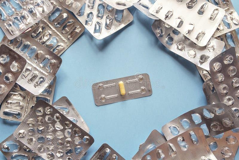 Um comprimido cercado por blocos de bolha vazios Conceito da panaceia fotografia de stock