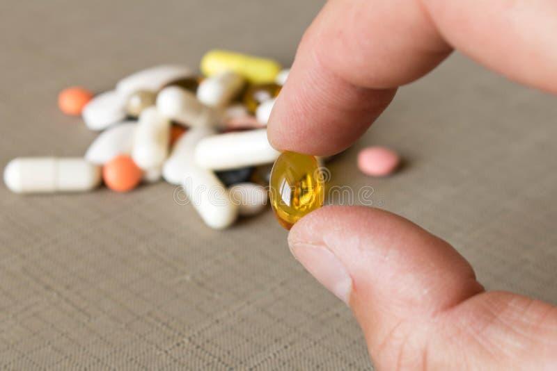 Um comprimido nas mãos humanas no fundo de uma pilha dos comprimidos E fotografia de stock