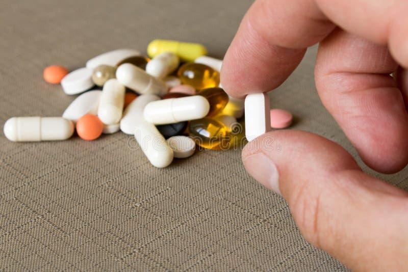 Um comprimido nas mãos humanas no fundo de uma pilha dos comprimidos E foto de stock royalty free