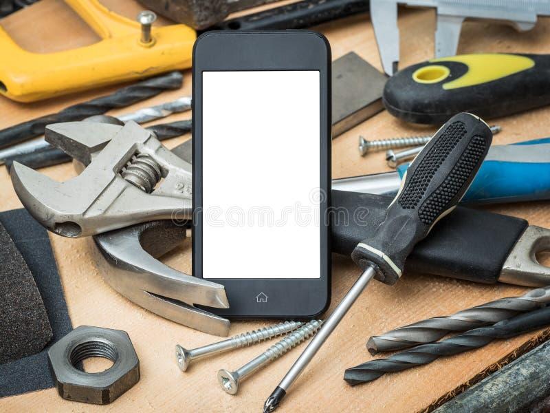 Um conceito com ferramentas da construção e um smartphone para afixar sua ideia fotografia de stock royalty free