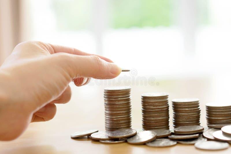 Um conceito do dinheiro da economia, mão masculina que põe o crescimento da pilha da moeda do dinheiro fotos de stock royalty free