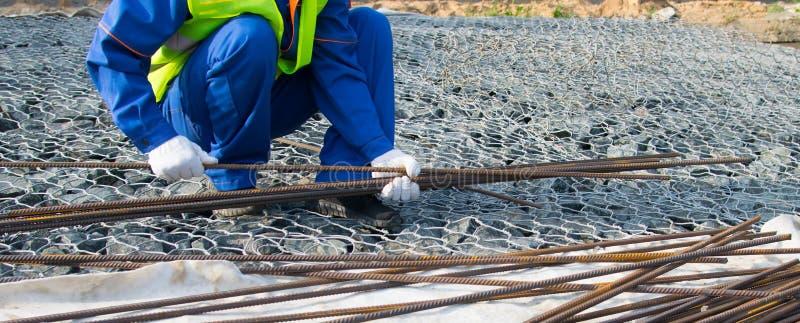 Um construtor em um uniforme azul, na perspectiva das pedras, toma as hastes de metal longas para a construção de estruturas conc fotografia de stock royalty free