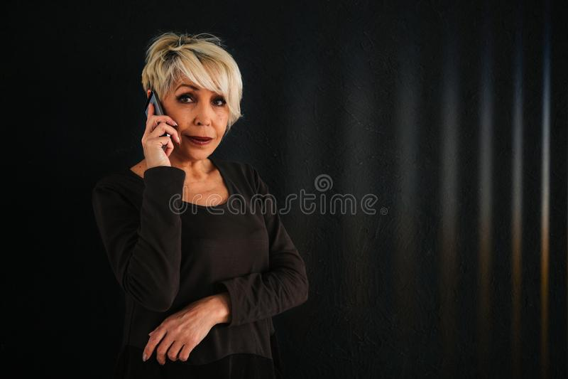 Um consultante fêmea idoso positivo bem sucedido está negociando um telefone celular Uma comunicação entre a utilização dos povos fotografia de stock