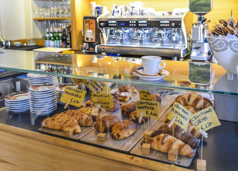 Um contador italiano do café da manhã com sabores diferentes do croissant Máquina do café no fundo foto de stock