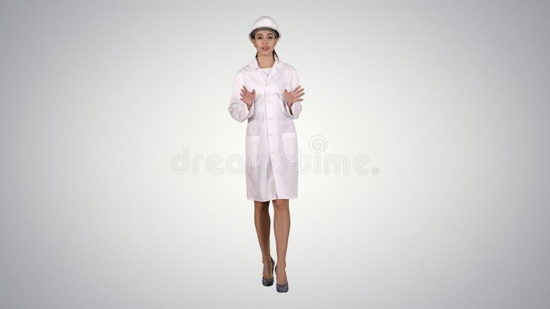 Um coordenador bonito novo do cientista da mulher na leitura de doa??o branca no fundo do inclina? foto de stock