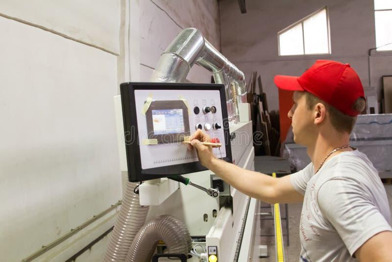 Um coordenador masculino controla o trabalho da máquina na loja da mobília fotografia de stock royalty free